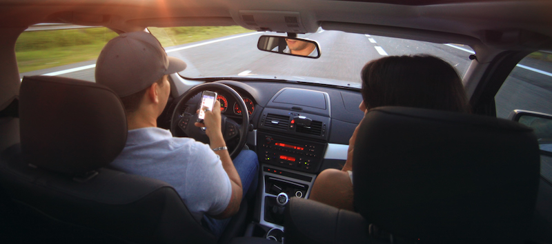 distracted driving awareness - man holding cell phone while driving